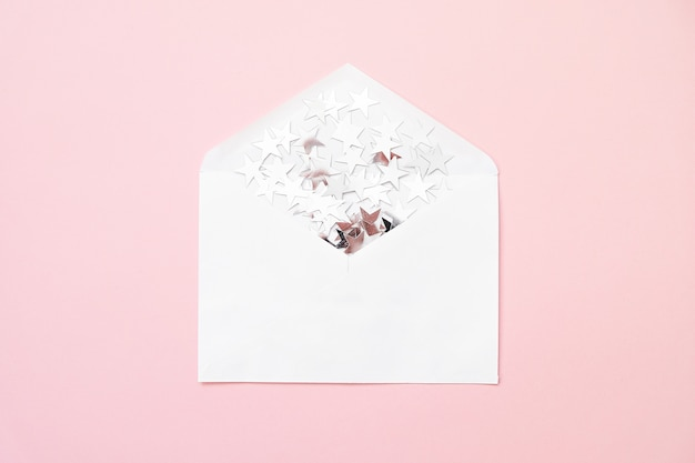 Silver star sprinkles confetti in envelope on pink background. minimal christmas.