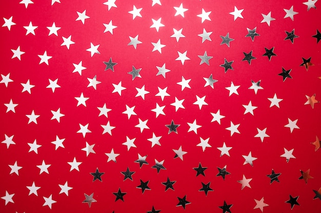 Silver star sprinkles on red backgound. festive holiday confetti. celebration concept.