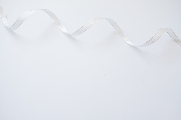 Silver streamers serpentine on pastel blue background. christmas gift.