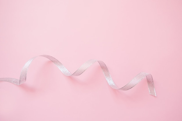 Silver streamers serpentine on pastel pink background. christmas gift.