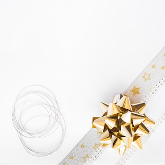 Silver string and ribbon bow on white background
