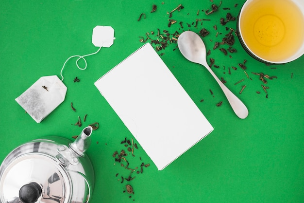 Silver teapot, spoon and herbal tea on green background