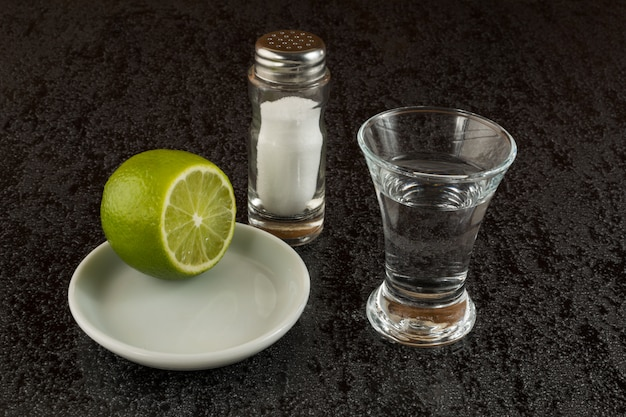 Silver tequila with lime on black background