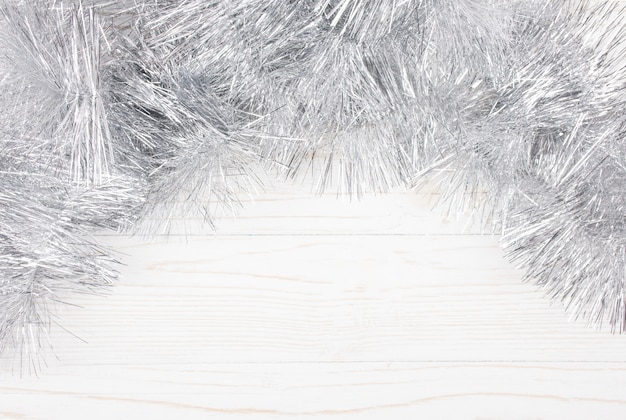 Silver tinsel on a white wooden background
