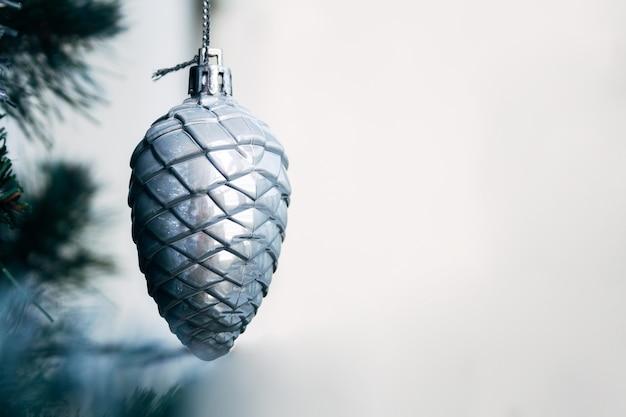 コピースペースと人工的なクリスマスツリーの銀のおもちゃの円錐形