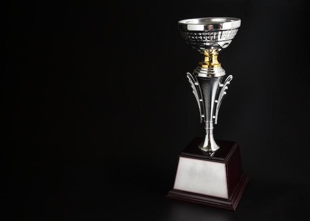 Silver trophy over black background. winning awards with copy space for text and design.