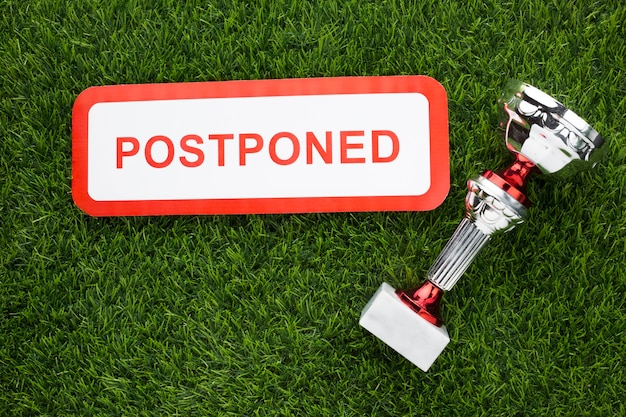Silver trophy next to postponed sign
