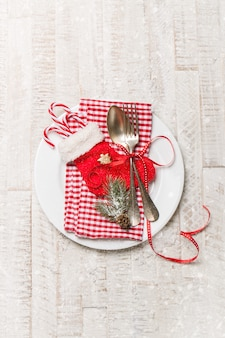 Silver vintage cutlery on a plate with christmas decoration and snow on a background, top view