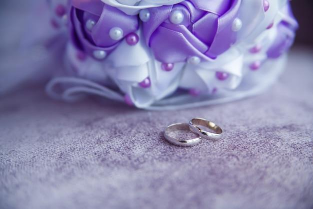 은색 결혼 반지와 라일락 배경의 웨딩 부케