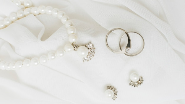 Silver wedding rings; earrings and pearl necklace on white lace