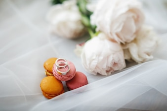 Silver wedding rings lie by white bouquet on the floor