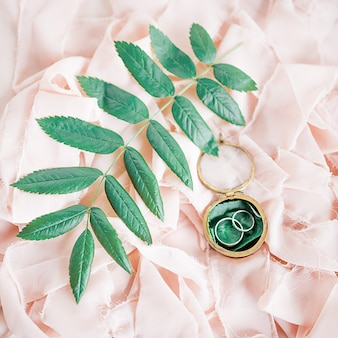 Silver wedding rings lie on the pink cloth among green leaves