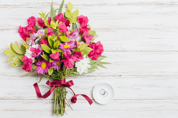 Silver wedding rings on white plate near the colorful bouquet on wooden backdrop