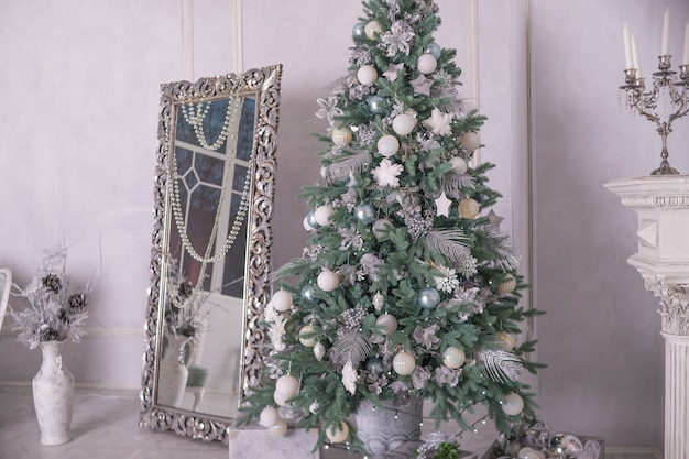 Silver and white balls. christmas tree with gifts in luxury interior. new year at home.christmas interior with big mirror and christmas decoration, ornaments. winter holidays living room