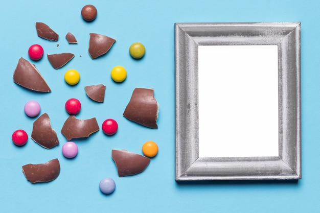 Silver white blank frame near the broken easter egg shells and gem candies on blue background