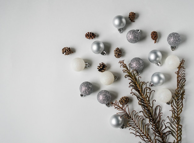 Silver and white christmas ball, cones and dry fern branch flat lay.