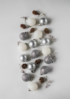 Silver and white christmas ball, cones and dry flowers branch flat lay.