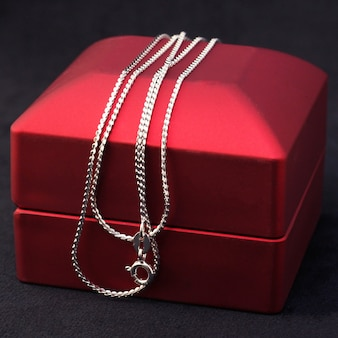Silver or white gold jewelry chain on a red gift box.