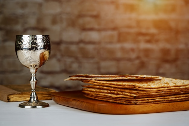 Silver wine cup with matzah, jewish symbols for the passover pesach holiday. passover concept.