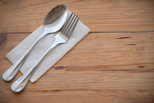 シルバーウェア、フォークスプーン、紙、左手に置かれた木製のダイニングテーブルに置く右のイメージにコピースペースを作るために焦点を合わせた食品コンセプトの背景