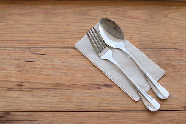 シルバーウェア、フォークスプーン、紙、左手に置かれた木製のダイニングテーブルに置く右のイメージにコピースペースを作るために焦点を合わせる食品コンセプトの背景