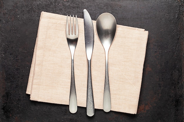 Silverware and napkin lying on old rustic