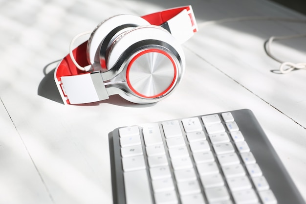 Silvery headphones with red inserts lie on a white desk with a keyboard