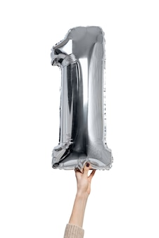 Silvery inflatable figure one in a female hands. close-up. isolate on white background.