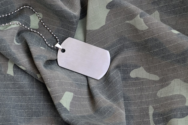 Silvery military beads with dog tag on camouflage fatigue uniform