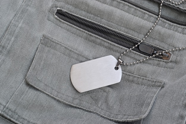 Silvery military beads with dog tag on dark grey vest with pockets