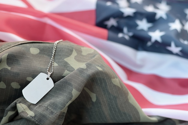 Silvery military beads with dog tag on united states fabric flag and camouflage uniform. memorial day concept