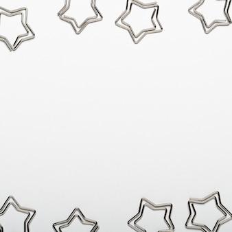 灰色の背景に星の形の銀色のペーパークリップ。オフィス文具のフレーム。コピースペース、平面図、フラットレイアウト。