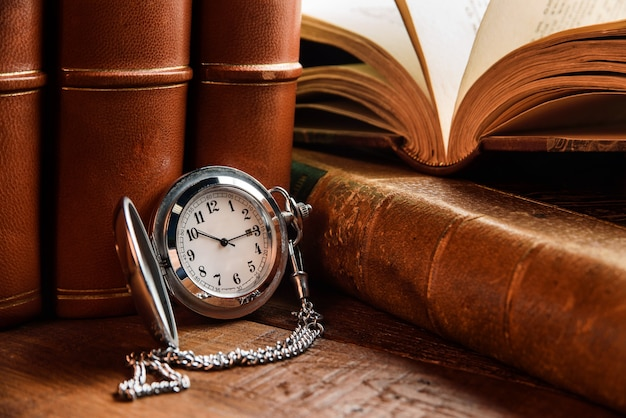 Silvery pocket watch and antique books in leather preplot on a wooden table close-up