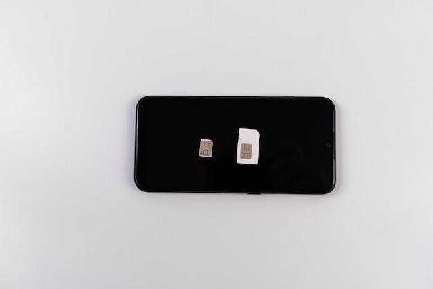 Simカード、白い背景の上の黒いスマートフォンのキークリップ。モバイル通信。ワイヤレス3g、4gインターネット。
