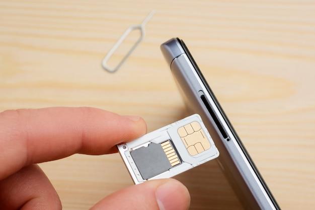 Simカードとメモリドライブのトレイを携帯電話に挿入する男