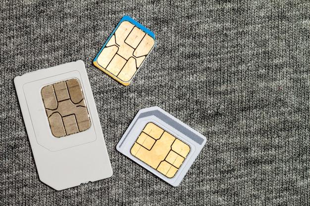 ミニ、マイクロ、ナノsimcardのセット。灰色の布のテクスチャに分離