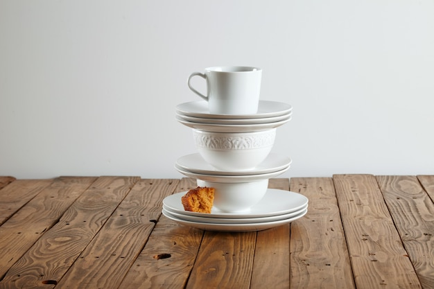 Similar but different white t-cups perched on top of each other with a tiny bit of light brown sponge cake on saucer
