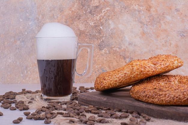 Simit은 음료와 커피 원두 한 잔과 함께 나무 판에 굴러갑니다.