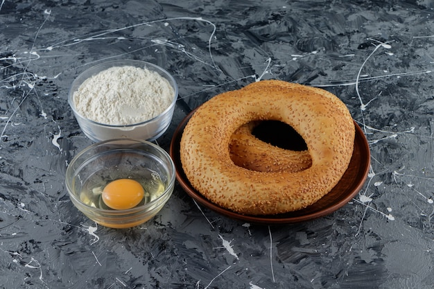Симит с семенами кунжута и стеклянной миской муки с сырым куриным яйцом.