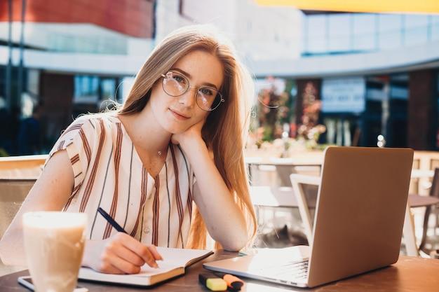 Симпатичная дама с рыжими волосами и веснушками что-то пишет во время перерыва на кофе на своем ноутбуке
