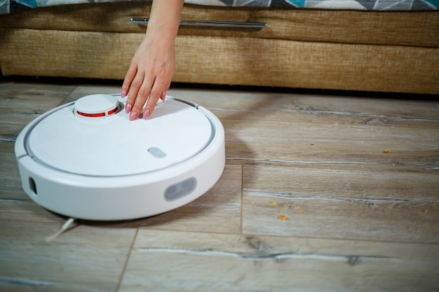 家庭用の最新技術によるシンプルで簡単な掃除。掃除機が家の掃除をしている間、女の子はお茶を飲んで休憩します Premium写真