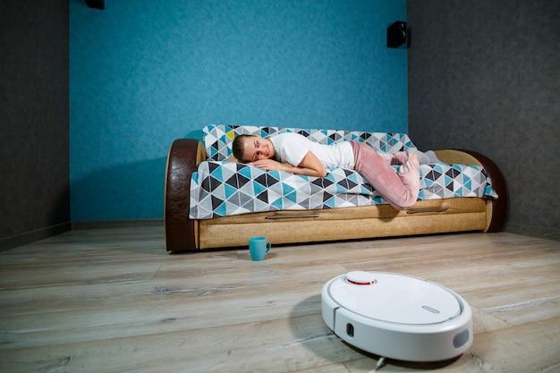 家庭用の最新技術によるシンプルで簡単な掃除。掃除機が家の掃除をしている間、女の子はお茶を飲んで休憩します
