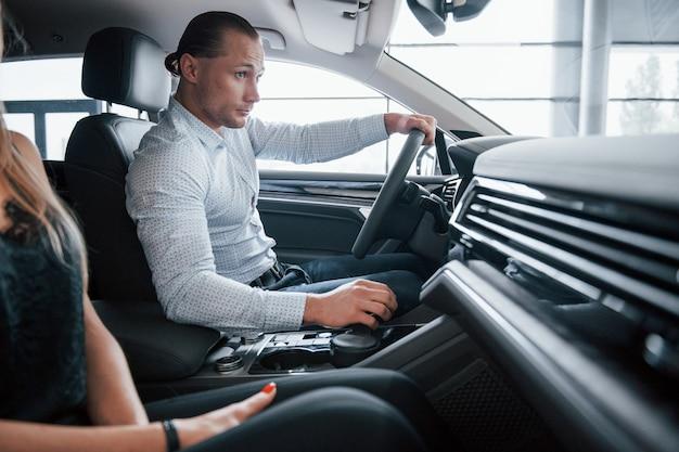 Простой и приятный интерьер. позитивный менеджер, показывающий покупательнице особенности нового автомобиля