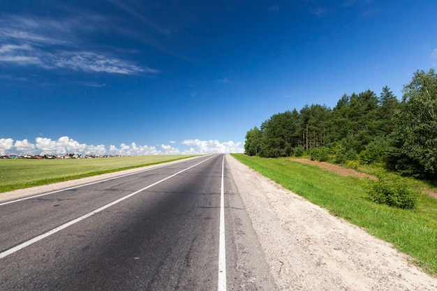Простая асфальтированная дорога с белой разметкой для регулирования движения, летний пейзаж с голубым небом, травой и деревьями