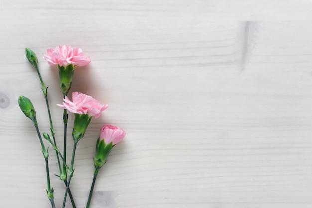Простой фон с тремя розовыми цветами и пустым пространством на деревянном