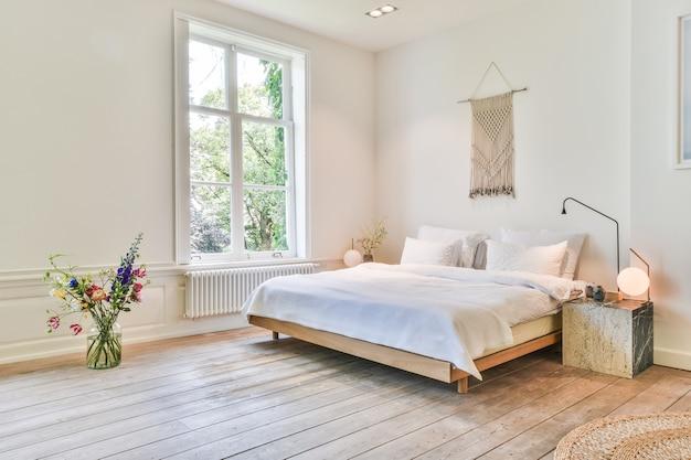 흰색 벽과 나무 바닥이있는 넓은 침실에 흰색 린넨이 깔린 심플한 침대는 마크라메 벽걸이와 꽃병으로 장식되어 있습니다.