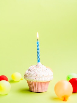 Simple birthday muffin with candle and balloons