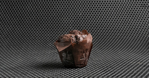 A simple black chocolate muffin dessert traditional food abstract isolated object on the color background