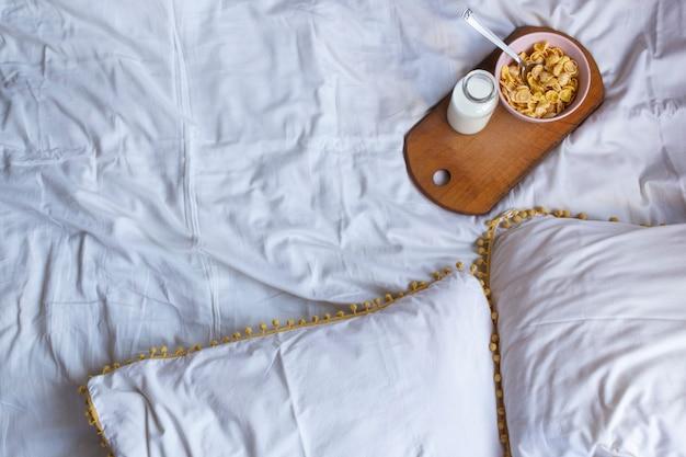 木製の机の上にコーンフレークとミルクを入れたベッドでのシンプルな朝食。黄色と白の色。フラットレイ、コピースペース