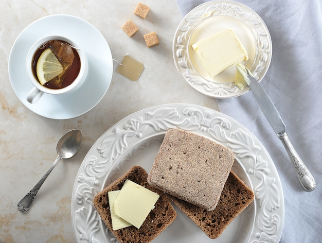 Simple breakfast   tea bags with lemon and rye bread with butte